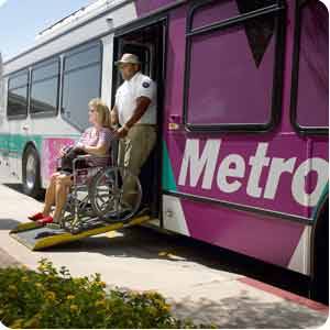 photo of bus operator assisting a person in a wheelchair exiting bus
