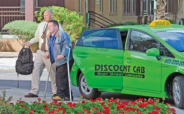Image showing driver assisting customer from green discount cab