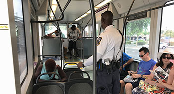 Fare inspector checking tickets on light rail during a sweep with Phoenix PD.