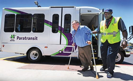 Man using crutches exiting a paratransit vehicle