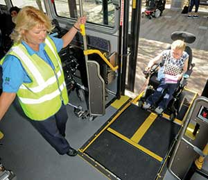 Bus operator assists customer in wheelchair onto the bus.