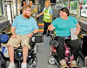 Image shows two riders in wheelchairs on bus.