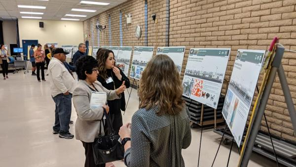 People looking at project boards at the South Central Extension public meeting