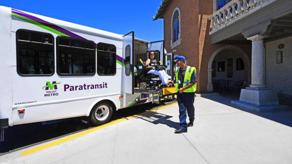 paratransit rider in wheelchair on vehicle lift helped by operator