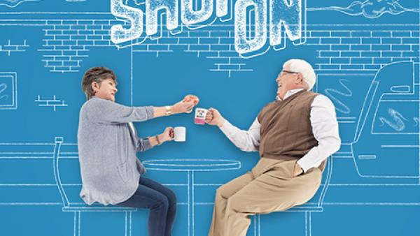 Older couple drinking coffee and eating donuts in a coffee shop