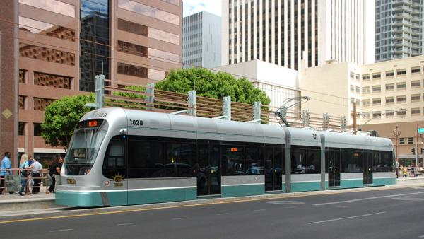 Light rail train in front of buildings