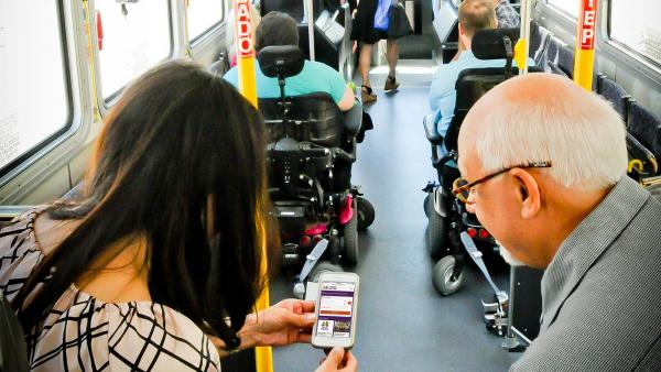 Couple sits on bus looking at the new website on their phone