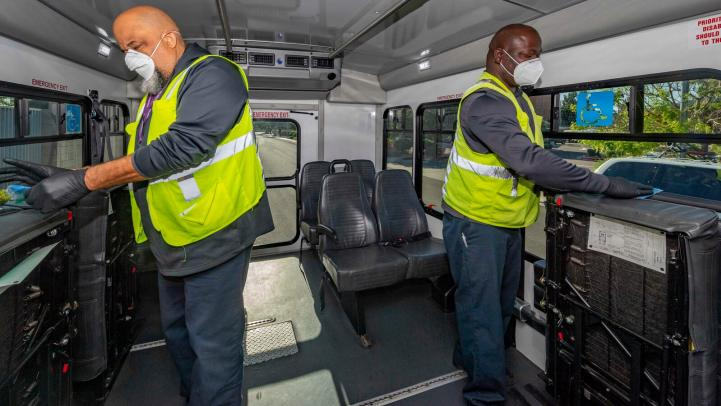 Two maintenance crew members disinfect a Paratransit vehicle