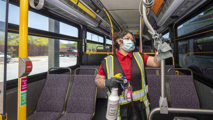 Woman in face covering cleans bus