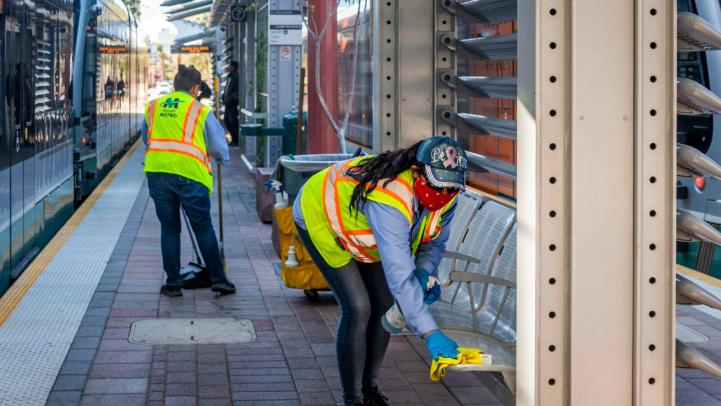 Two people clean the light rail platform