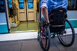 man on wheelchair boarding light rail vehicle with crowd