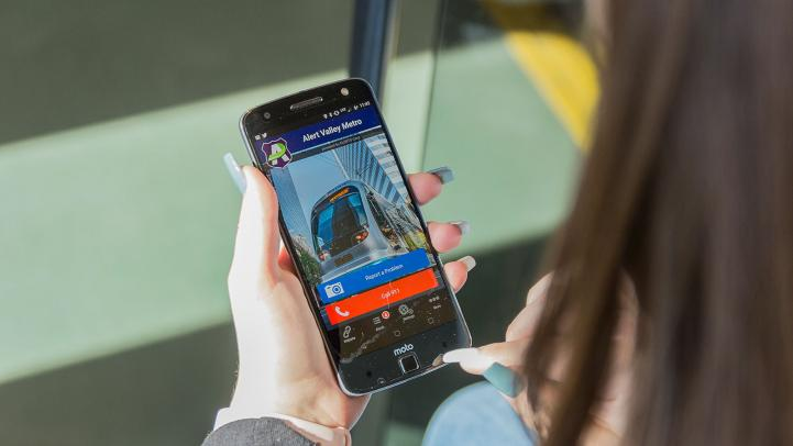 Woman holding smartphone with Alert Valley Metro opened