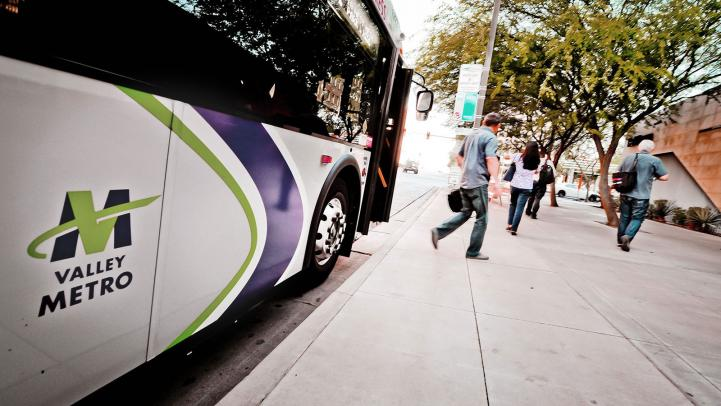 riders deboarding bus with Valley Metro logo on side