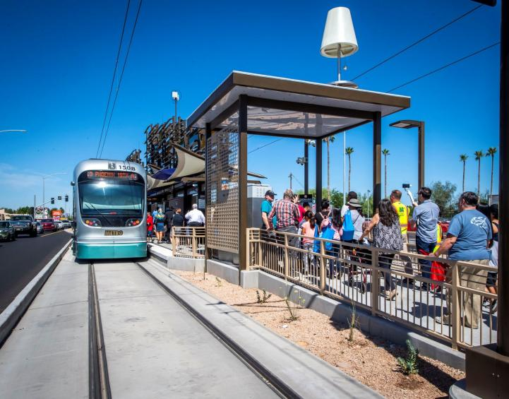Photo of passengers at Gilbert Road Station approaching light rail train during the May 18th opening celebration.