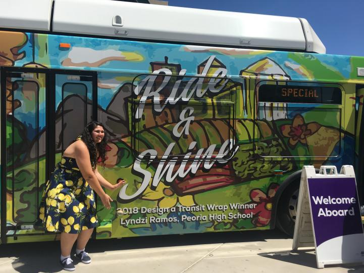Design a transit wrap winner posing in front of bus with her wrap.