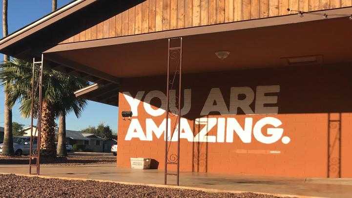 Text: You Are Amazing painted on a side of home under carport