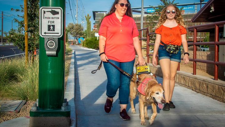 Two women walking with a service dog