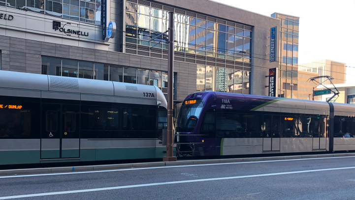 two light rail trains tethered. On ein silver and green paint, the second in purple and silver paint