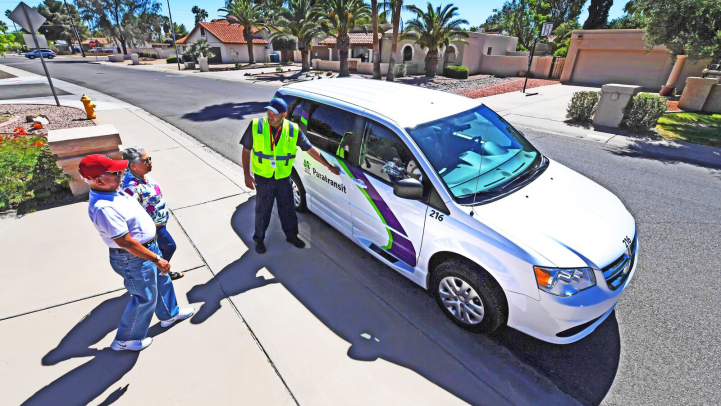 Paratransit driver opening vehicle door for elderly couple