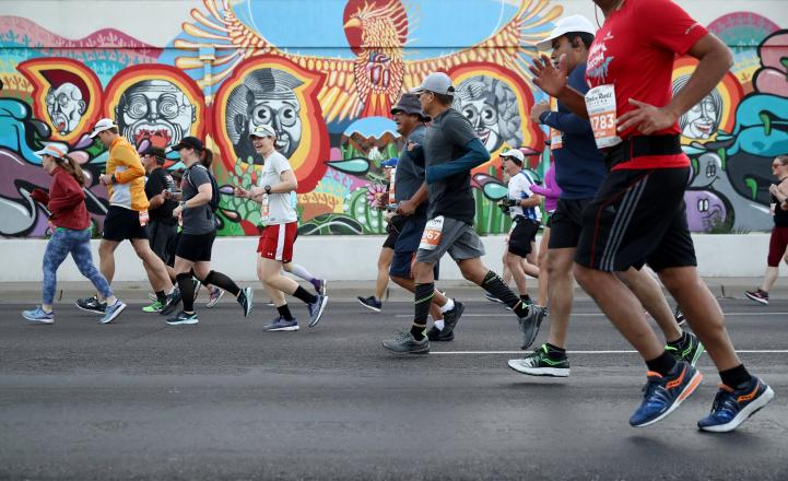 feet of runners in front of colorful mural