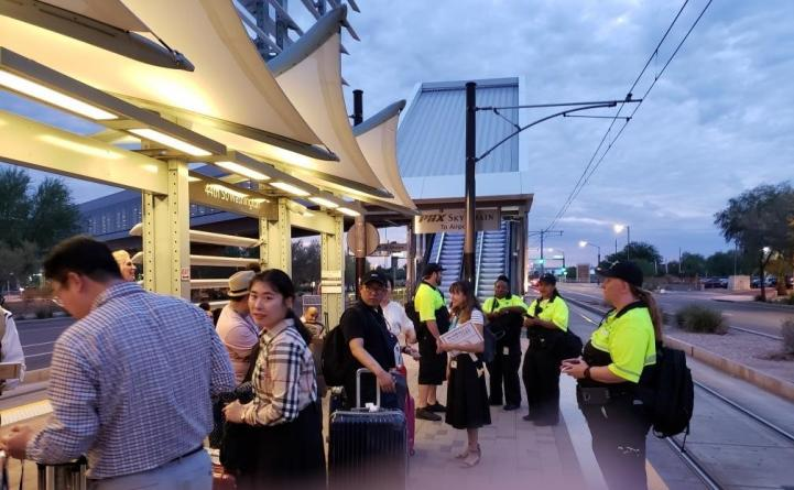 Light rail riders and Customer Experience Coordinators stand at a light rail station