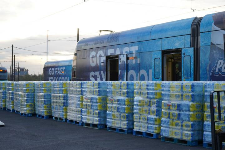 Pallets of water stacked in front of train