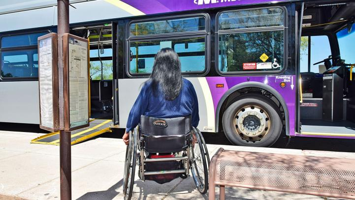 Woman in wheelchair boards bus