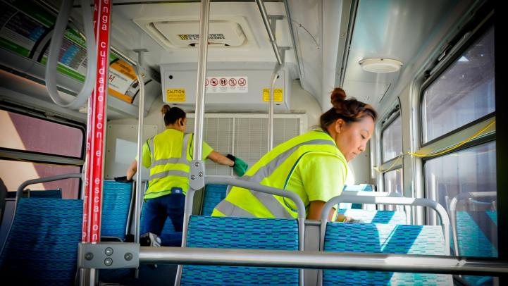Two maintenance workers clean the bus