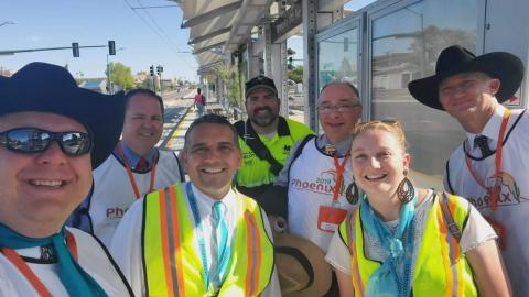 Jehovah's Witness Convention attendees stand at a light rail station with a Customer Experience Coordinator
