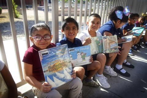 Thew Elementary students next to fence holding new books