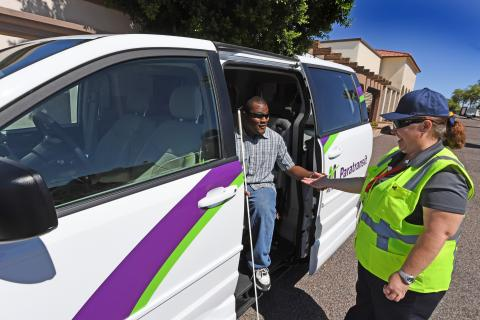 blind man being helped out of a van by paratransit driver