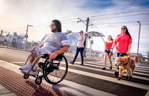 man in wheelchair and visually impaired rider exiting light rail staiton