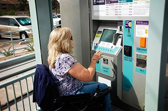 lady in wheelchair purchasing pass at a light rail station