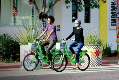 Two people riding Grid Bikes on a street