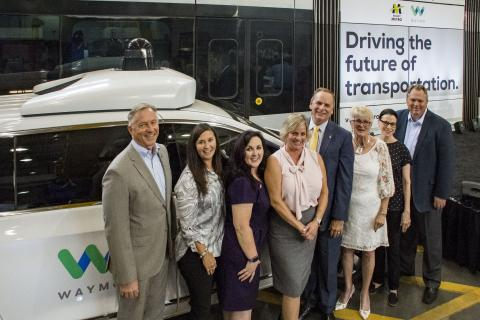 Valley Metro board members stand in front of self-driving Waymo vehicle