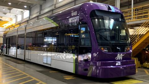 purple, silver and green light rail vehicle inside an industrial warehouse