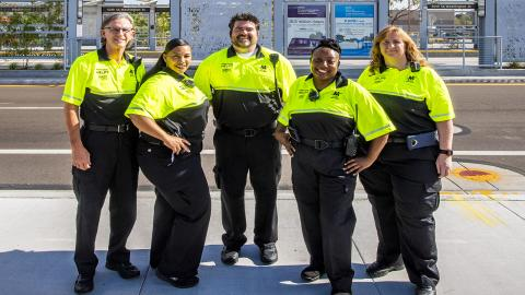 Five Customer Experience Coordinators in yellow and black uniforms
