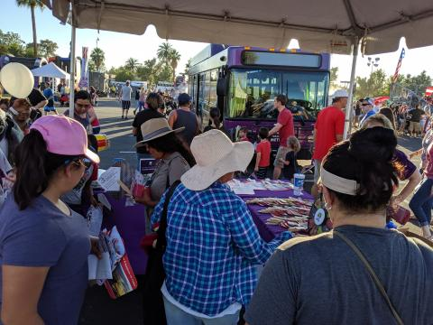 People interact with a Valley Metro booth at the Arizona Celebration of Freedom