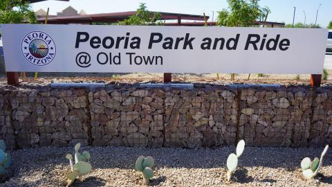 "Rock wall and cactus landscaping. Metal sign with text reads ""Peoria Park-and-Ride at Old Town"""