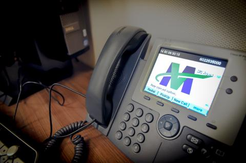 Phone at the Valley Metro call center. Valley metro logo is displayed on the digital screen.