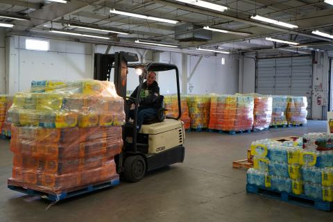 United Food Bank forklift operator with pallet of donated water