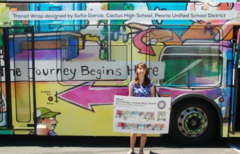 The 2017 Design a Transit Wrap winner next to a bus wrapped in her design