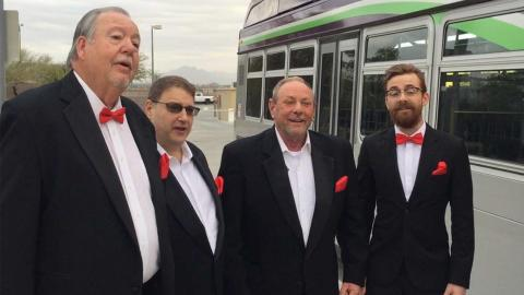 Rob Murray and his barbershop quartet in front of bus