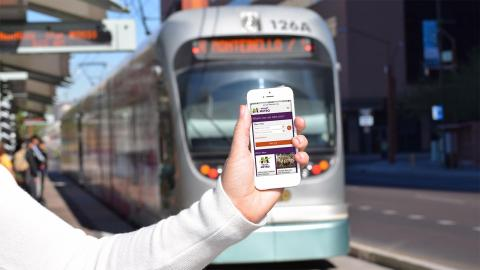 Cellphone shows new website with light rail train in the background