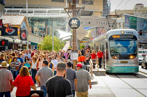 Valley Metro train and crowd on sidewalks