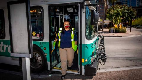 Bus operator wearing a face covering exiting front door