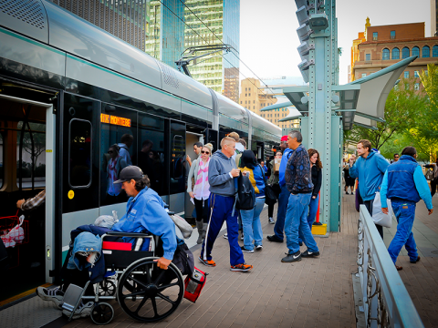 man on wheelchair shown boarding light rail vehicle with crowd in background